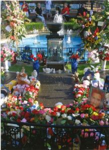 Memorial to Elvis Presley on the grounds of Graceland with flowers and stuffed animals all around it.