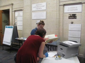 Two women hard at work examining several pieces of archival materials at a table with a grey bankers box on it.