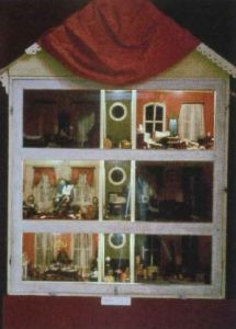 A three story dollhouse with six rooms and a central small area on each level.