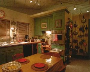 View of the interior of Julia Child's kitchen with green painted cabinets and a couple of paintings hung on the cabinet doors, two windows with wooden blinds pulled shut, a long rectangular table in the center and a lot of pots and pans hung on a wall behind the cabinet wall.