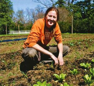 A woman crouches down in a field of growing beans.