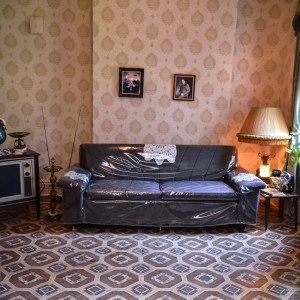 View of the interior of one of the Tenement Museums exhibits with a couch covered in clear plastic sitting on a patterned rug with a side table and lamp to the right and a 1960s television to the left. The walls have a patterned wallpaper.