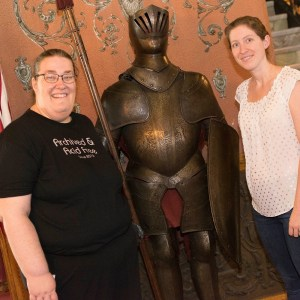 Two women pose with a knight in shining armor.