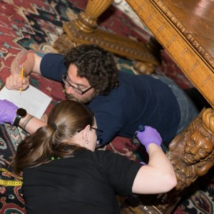 A man lays under an intricately carved table on his stomach filling out a piece of paper and a woman lays near him examining one of the legs.