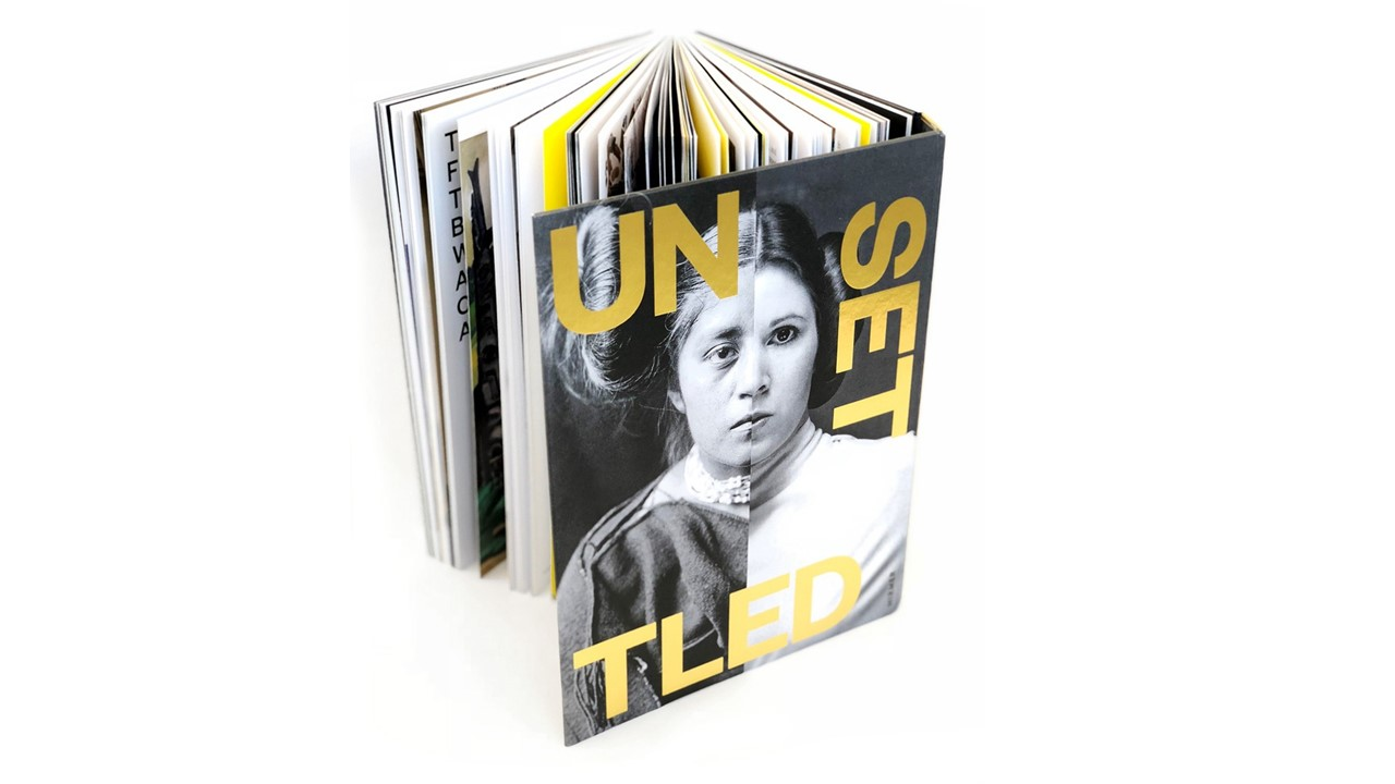 View of the Unsettled book standing open on a white background.