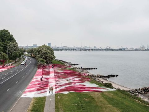 View of the exterior of the museum grounds with a road and the art installation crossing the road.
