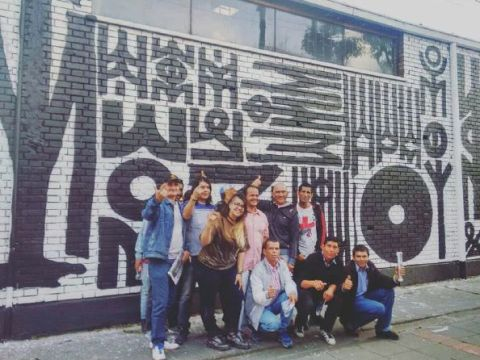 A group of people stand in front of a wall mural posing for a picture.