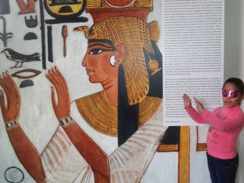 A young girl mimicks the Egyptian hygroglyph depicted in a large wall panel in a museum exhibition.