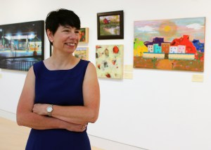 a woman in a blue dress standing in front of artwork on the wall