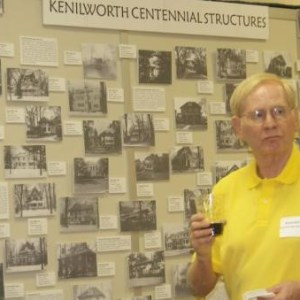 A white man in a yellow collared short sleeve shirt wearing a nametag stands in front and to the right of a wall with the words Kenilworth Centennial Structures and various black and white pictures mounted on it.