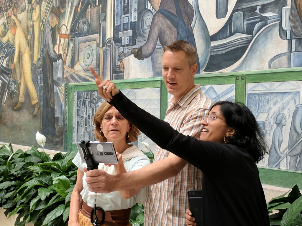 A white man stands in between one white woman and one brown woman holding a cell phone on a holster out in front of him, one of the women points to an object out of view.