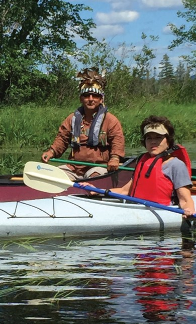A man sits in a canoe with a feathered headress on and a woman sits in a separate canoe wearing a tan visor and life vest.