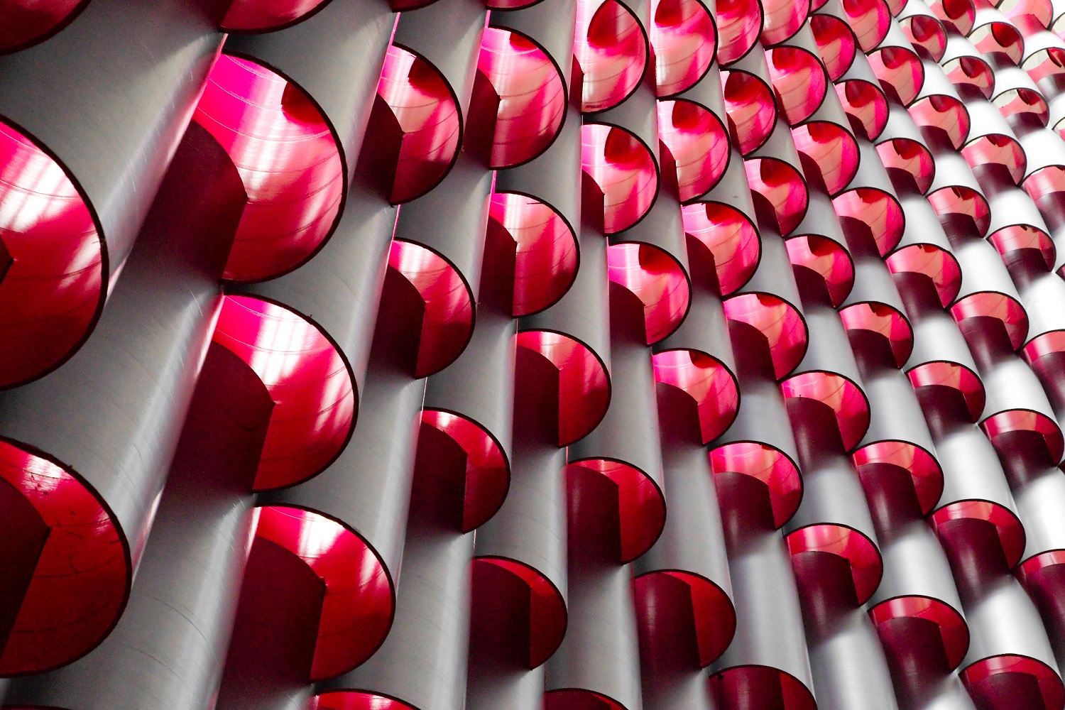 Round tubes stacked on top of each other with bright pink interiors creating a glowing tower.