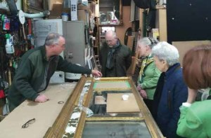 Frame conservator Bill Adair describes his work to Dumbarton House staff and volunteers at his studio. At Dumbarton House, acquisition and conservation of collections items, like this tri-part over-mantel looking glass, are funded through a mix of contributed and earned income.