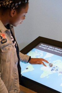 A young black woman using her fingers to manipulate the interactive map on a kiosk screen.