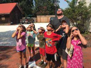 A group of young children an done adult look up at the sun wearing solar glasses.