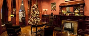 """A photo of the interior of the Richard H. Driehaus Museum, the site of the panel discussion """"How can I better support my LGBTQ co-workers,"""" comprised of LGBTQ museum staff and part of CAMP's meeting schedule. The photo shows a sitting room with table and chairs, a fireplace, and a Christmas tree."""