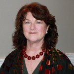 Image of a white woman with shoulder length wavy reddish brown hair wearing a large red beaded necklace.