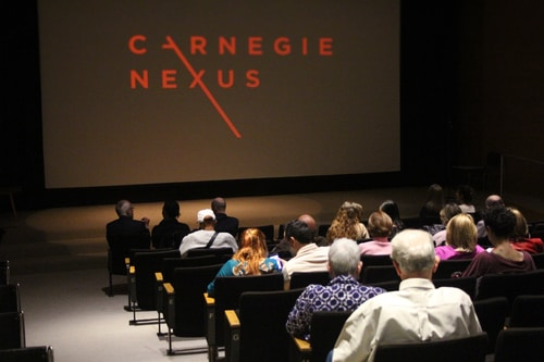 """An auditorium of people look at a screen with the logo for """"Carnegie Nexus"""" on it."""
