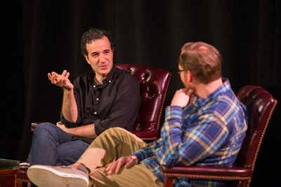 Two men seated and having a conversation on stage.