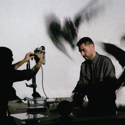 Two men stand on stage in front of a desk with equipment on it. Behind them is a projection of birds in flight.