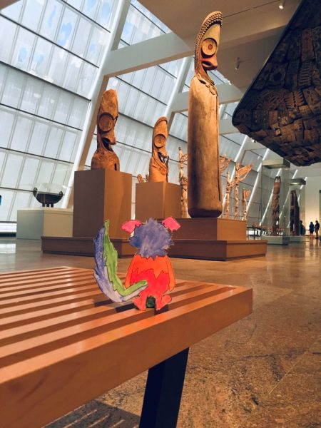Marabou is seen from behind, perched on a slatted museum bench in front of a collection of wood scupltures from Oceania.