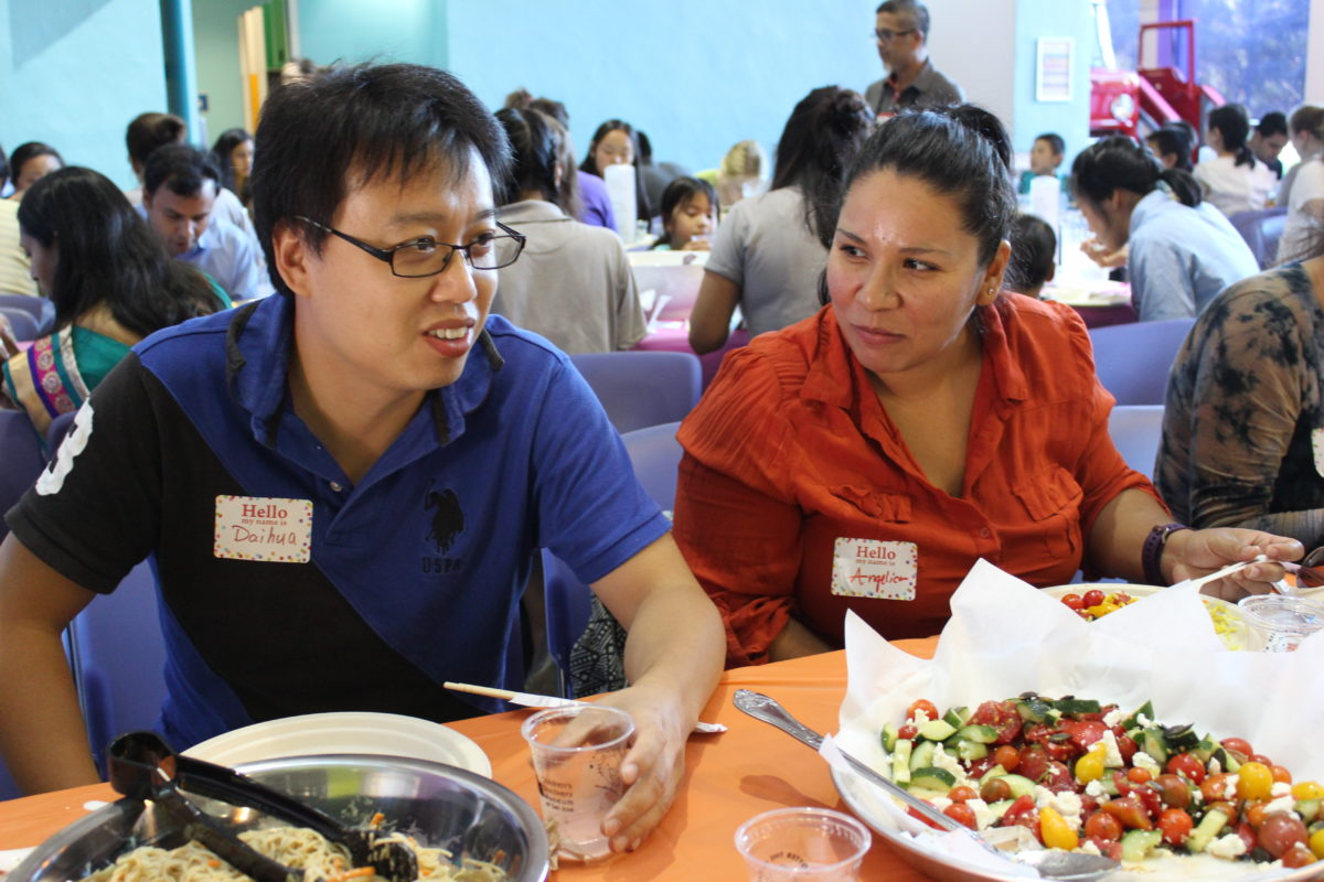 An Asian man sits next to a Latina woman at a meal, engaged in conversation.