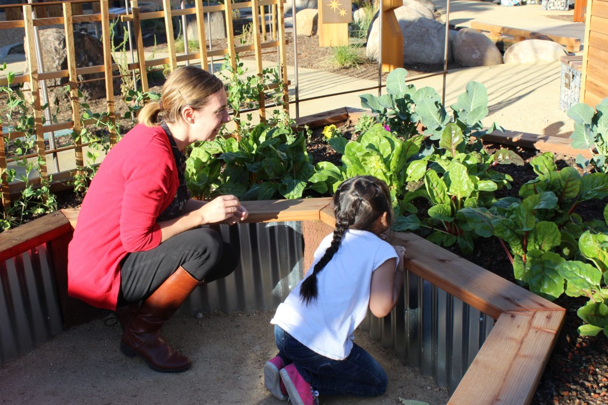 An adult woman crouches with a young visitor to look at vegetables growing in a garden.