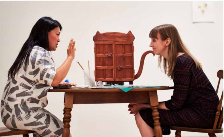 Two women sits at a wooden table with a wooden case shaped like a cat sitting between them.