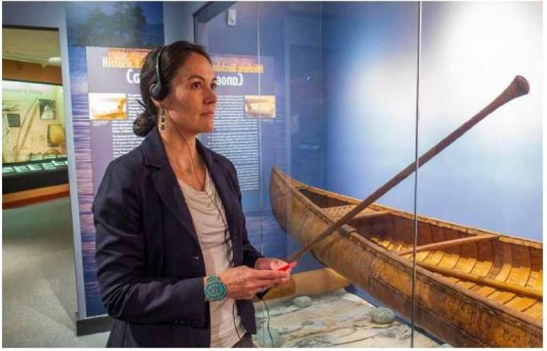 Shelly Lowe stands in front of a glass enclosed canoe on display with a set of headphones on.