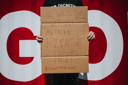 "Cardboard sign that says ""I will DIE without medicine, please help #DignityMuseum"""