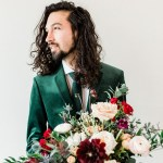 Image of Matthew Ramirez standing behind a bouquet of beautiful flowers wearing a green suit and tie. A white man with long dark brown hair with a beard and moustache looks off to the left into the distance.