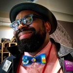Image of Saleem Penny, a black man wearing a bowler hat, blue rimmed glasses and a color bow tie.