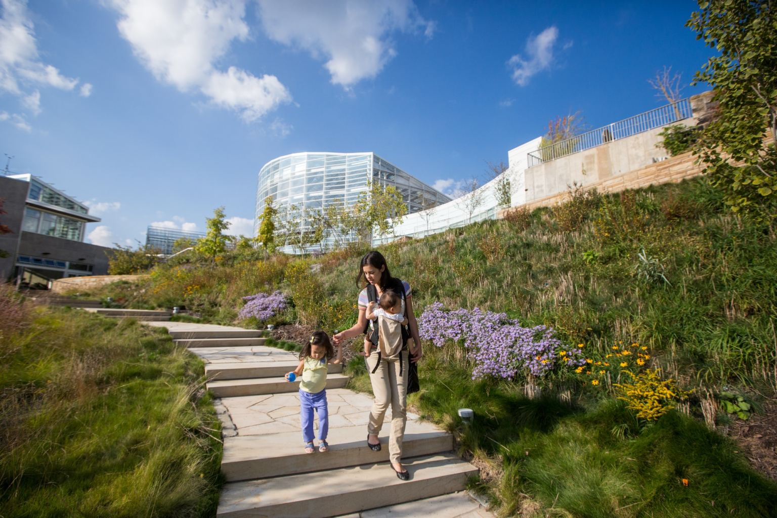 A mother with two small children walks down the steps of Phipps's nature walking tour next to the Center for Sustainable Landscapes.