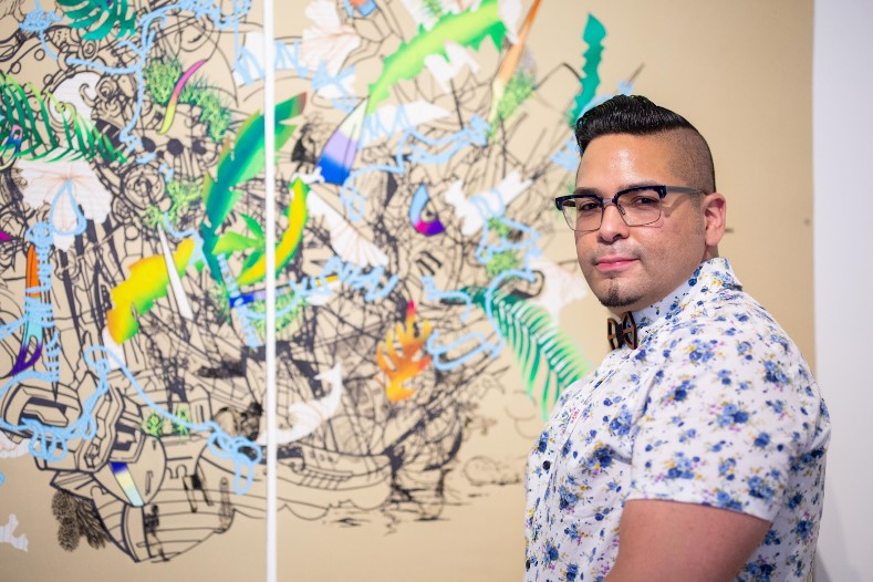 David Rios in front of a graphic print.