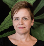 Woman with short brown hair, wearing black shirt in front of green leaf background