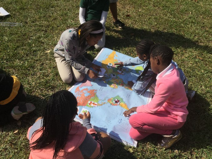 Several young visitors sit on the grass with a large map in between them.