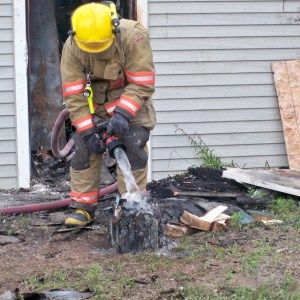 A firefighter is seen outdoors standing over a damaged artifact with a running hose.