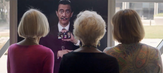 A group of three visitors is seen looking at the AI Dali, who holds a smartphone displaying a group selfie of himself and the visitors.