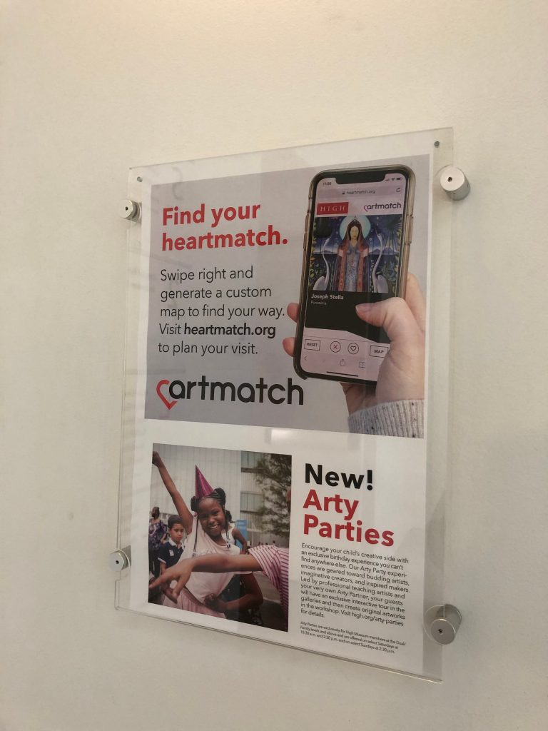 """An ad hung on a wall says """"Find your heartmatch. Swipe right and generate a custom map to find your way. Visit heartmatch.org to plan your visit."""""""