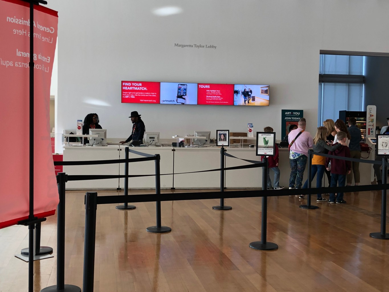 The ticket line in the lobby of the museum shows signs advertising Heartmatch on top of stanchions and on a TV screen behind the desk.