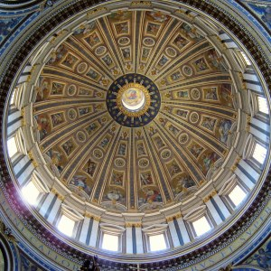 The interior view of a light-filled dome with intricately painted designs arcing up it in columns.