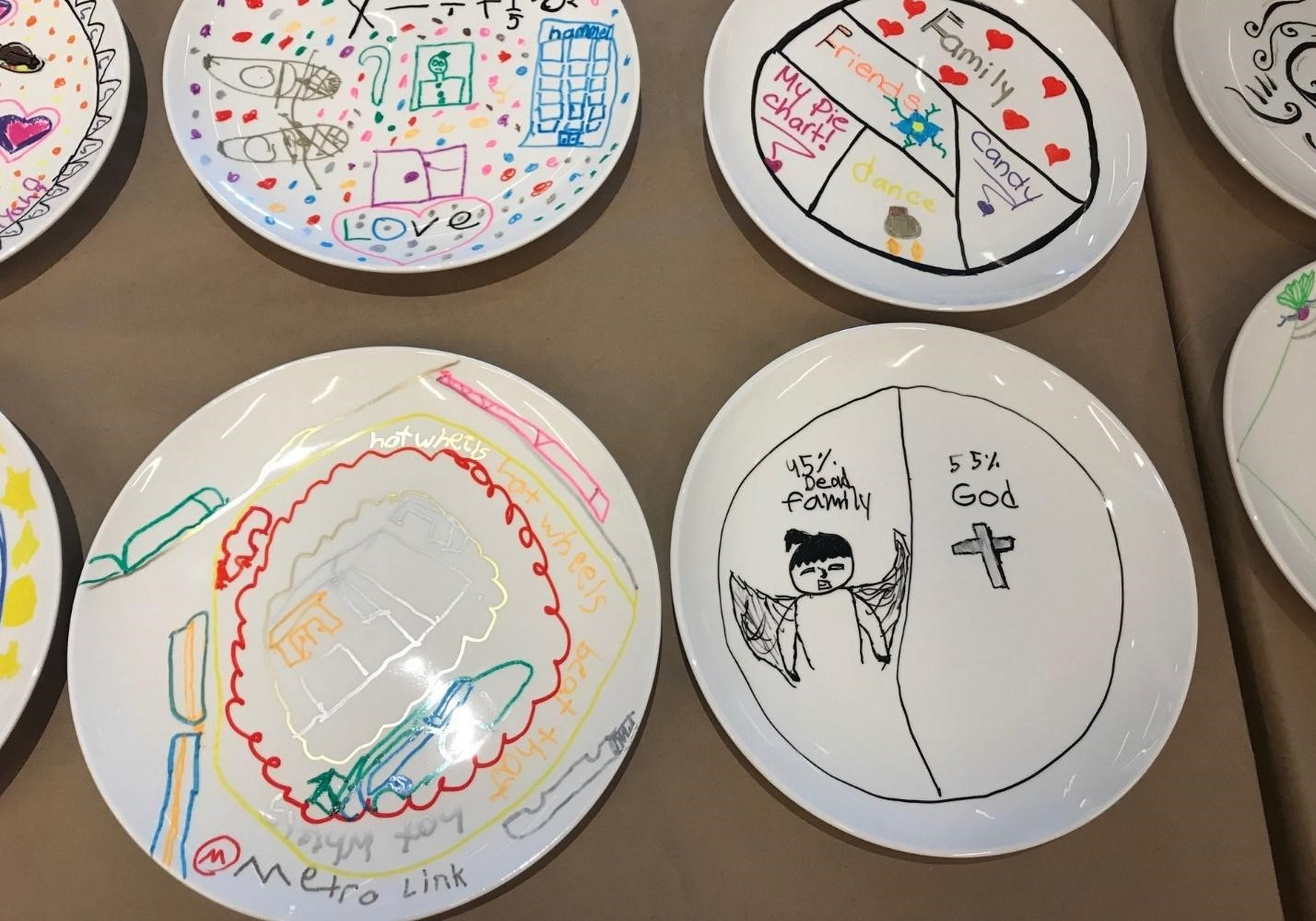 "Among more colorful, elaborately designed plates, the grieving student's is shown: a simple black pie chart that says ""45% dead family"" and ""55% God,"" with illustrations of an angel and a crucifix."
