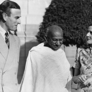 A black-and-white photograph of Gandhi posed with English royalty.