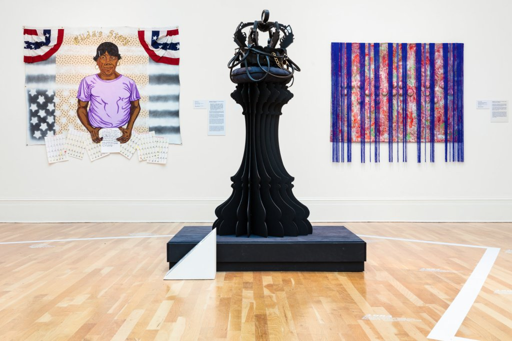 Three pieces of art in a museum gallery: one portrait of a subject in front of an American flag, one canvas with blue fringe hanging from it, and one large sculpture resembling a chess piece