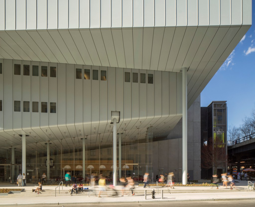 The exterior of a museum building abutting the sidewalk, where crowds are seen walking by, and from which the lobby of the museum can be seen behind glass windows.
