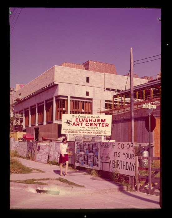 "A historical photo of an under-construction building with a plywood wall surrounding it covered in handwritten signs that say things like, ""Wake Up Co-op It's Your Birthday!"""