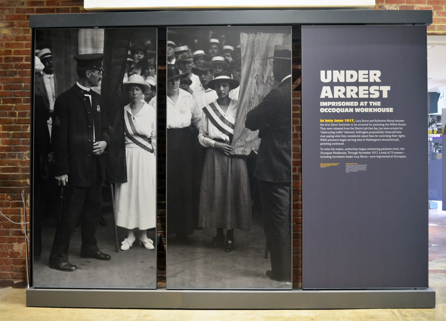 """A panel display in a museum showing photos of suffragists facing uniformed men. The text reads """"Under Arrest: Imprisoned at the Occoquan Workhouse."""""""