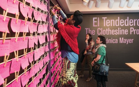 A woman stands on a step stool and clips a pink piece of paper to a wire with hundreds of other pink notes hang.