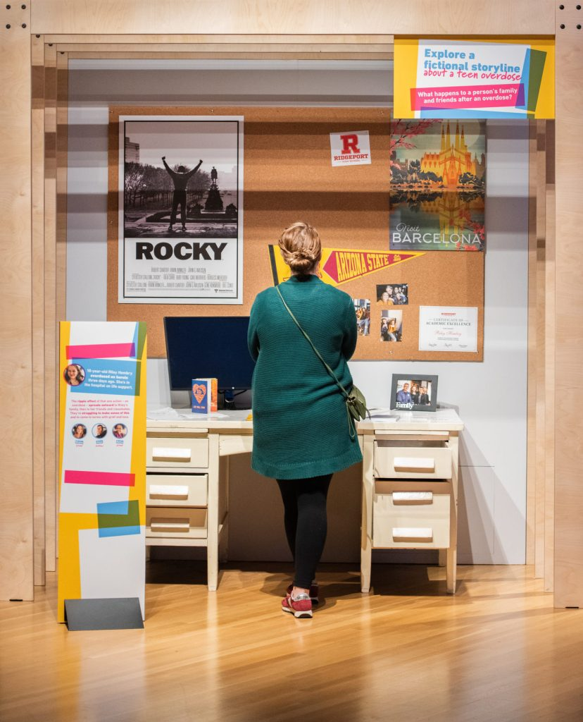 "A visitor looking at a display set up to resemble a desk space, with a computer and family photo on the desktop and mementos like posters and college flags on a cork board above. A sign reads, ""Explore a fictional storyline about a teen overdose."""